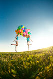 Kvinnor för lycklig födelsedag mot himlen med regnbåge-färgade luftlodisar Royaltyfri Fotografi