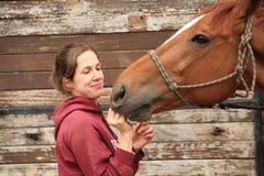Kvinnor ger ett äpple till henne hästen Royaltyfri Foto