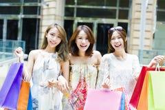 Kvinnor grupperar bärande shoppingpåsar på gatan Fotografering för Bildbyråer