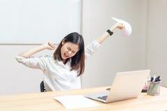 Kvinnor har ett tillbaka att smärta på grund av datoren och arbetet på länge royaltyfri foto