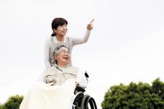 Kvinnor hjälpte rullstolen Arkivbild