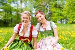 Kvinnor i bayersk kläder eller dirndl på en äng royaltyfria bilder