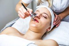 Kvinnor i cosmetologykabinett Cosmetologisten gör tillvägagångssättet för ung flicka Arkivbild