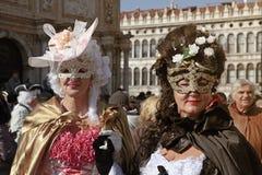 Kvinnor i den venetian karnevaldräkten som poserar på San Marco fyrkant, C Royaltyfri Bild