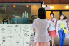 Kvinnor i den vita kappan som väntar ett kaffe Arkivbild