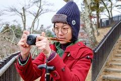 Kvinnor i det röda laget som tar ett foto på den Japan trädgården Royaltyfri Foto