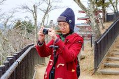 Kvinnor i det röda laget som tar ett foto på den Japan trädgården royaltyfria bilder