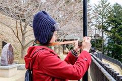 Kvinnor i det röda laget som tar ett foto på den Japan trädgården Royaltyfri Bild