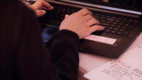 Kvinnor i en svart tröja skrivar snabbt ut på tangentbordet på bärbara datorn stock video