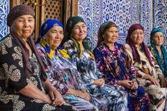 Kvinnor i färgrika klänningar som sitter och vilar i Khiva, Uzbekistan Arkivbild