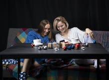 Kvinnor i hem- kläder dricker te Svart bakgrund arkivfoton