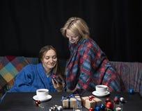 Kvinnor i hem- kläder dricker te Svart bakgrund arkivbilder