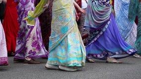 Kvinnor i hinduiska traditionella dräkter, dans och den sjungande hareKrishna mantraen arkivfilmer