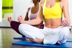 Kvinnor i idrottshallen som gör yoga, övar för kondition Arkivbilder