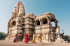 Kvinnor i indisk sari klär hållande ögonen på hinduiska tempel i Madhya Pradesh Lokal för Unesco-världsarv Fotografering för Bildbyråer