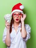 Kvinnor i julhatt med pengar Arkivbild