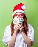Kvinnor i julhatt med pengar Arkivfoton