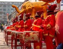 Kvinnor i röda guld- dräkter som trummar under ceremonieln av öppningen av ett lager i den Hunchun staden av Kina, Jilin arkivfoton