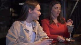 Kvinnor i rött sammanträde på stången med att förbluffa den märkes- metallkoppen med coctailen och ost på sauser och samtal till  lager videofilmer