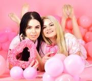Kvinnor i rosa pyjamas som poserar på kamera med rosa hjärtor medan lekmanna- near luftballonger på pajamaen, slummerparti över r Royaltyfria Bilder