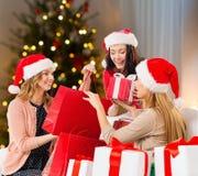 Kvinnor i santa hattar med gåvor på jul arkivbild