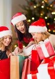 Kvinnor i santa hattar med gåvor på jul royaltyfri bild