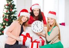 Kvinnor i santa hjälpredahattar med klockan som visar 12 Royaltyfri Foto