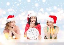 Kvinnor i santa hjälpredahattar med klockan som visar 12 Arkivbilder