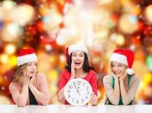 Kvinnor i santa hjälpredahattar med klockan som visar 12 Arkivfoto