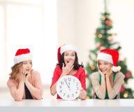 Kvinnor i santa hjälpredahattar med klockan som visar 12 Arkivfoton