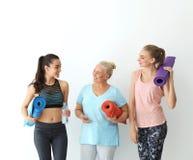 Kvinnor i sportswear med yogamats royaltyfri fotografi