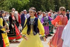 Kvinnor i Tatar nationell kläder dansar i en cirkel bland en folkmassa av folk royaltyfri fotografi