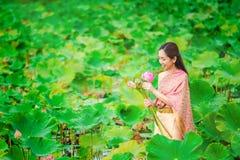 Kvinnor i thailändskt för klänningar för lotusblommablommor mot efterkrav fartyg arkivbilder