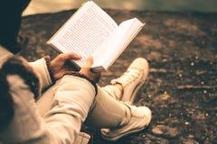 Kvinnor i vinter sitter läste den favorit- boken i ferien arkivbilder