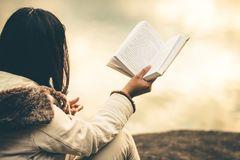 Kvinnor i vinter sitter läste den favorit- boken i ferien royaltyfri foto