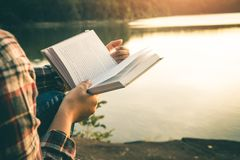 Kvinnor i vinter sitter läste den favorit- boken i ferien royaltyfri bild