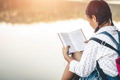 Kvinnor i vinter sitter läste den favorit- boken i ferien arkivbild