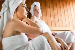 Kvinnor i wellnessbrunnsort som tycker om bastuavkoken Arkivbilder