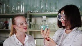 Kvinnor innehav och blandning av en flaska med en kemisk vikt lager videofilmer