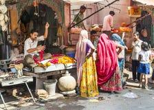 Kvinnor köper färgrika girlander på Arkivfoto