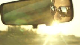 Kvinnor kör en bil på solnedgång Reflexionsframsida i spegel för bakre sikt av medlet stock video