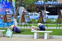 Kvinnor klipper gräs i en parkera i den Nha Trang staden royaltyfri fotografi