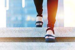 Kvinnor kliver framåtriktat till framgång, affär som unga kvinnor kliver framåtriktat på trappuppgång royaltyfri foto