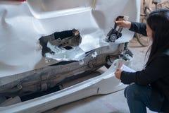 Kvinnor kontrollerar bilar för olyckor arkivbild