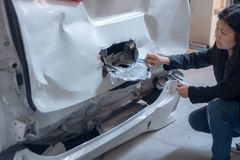 Kvinnor kontrollerar bilar för olyckor royaltyfria bilder