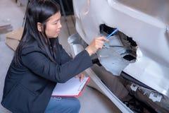 Kvinnor kontrollerar bilar för olyckor fotografering för bildbyråer