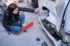 Kvinnor kontrollerar bilar för olyckor royaltyfri bild