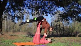 Kvinnor kopplar ihop praktiserande acroyoga i parkera på solnedgången arkivfilmer