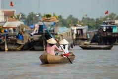 Kvinnor korsar Mekong River vid paddleboat på den berömda sväva marknaden i Cai Be, Vietnam Arkivfoton