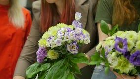 Kvinnor lär att göra blom- design under vägledningen av en professionell En grupp av unga kvinnor i gruppen av stock video